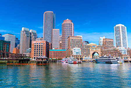 Boston cityscape reflected in water, skyscrapers and office buildings in downtown, view from Boston harbor, Massachusetts, USA Фото со стока