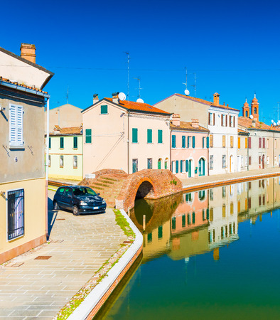 A street of the small Italian town of Comacchio. Colored houses reflected in water. Stone bridge and water canal in venetian style.