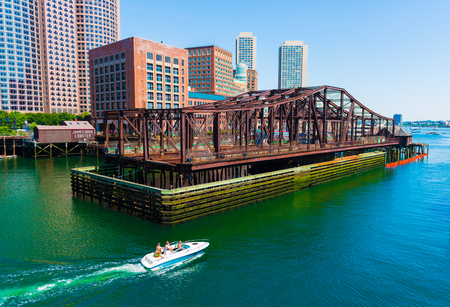 Boston - June 2016, MA, USA: Boat with people is floating on water from Boston harbor towards the open sea (ocean) Editorial