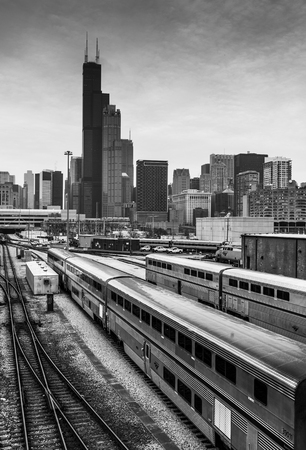 Chicago - March 2017, IL, USA: Chicago skyline at cloudy day. Railroad tracks with train, office buildings in downtown and the Willis (Sears) Tower.