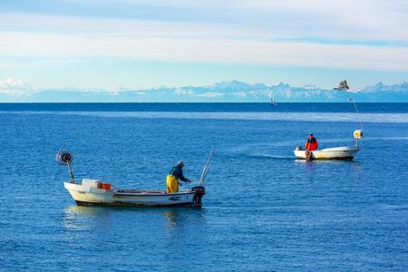 Piran - November 2013, Slovenia: Two fishermen in boats, Adriatic Sea, mountain range on the background