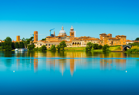 Mantova, Italy: Cityscape reflected in water. Old Italian town skyline. Province of Lombardy.