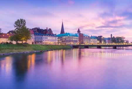 Schöner Sonnenuntergang in Malmö, Schweden. Malerischer Blick auf eine alte europäische Stadt am Abend. Skyline spiegelt sich im Wasser. Fotografie mit Langzeitbelichtung
