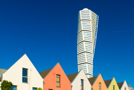 Malmo - October 2018, Sweden: View of The Turning Torso skyscraper with blue sky on the background and a row of colored residential houses in front Editorial