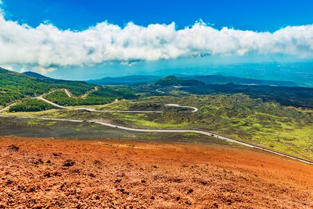 Picturesque landscape with serpentine road, colorful lava hills covered with grass and forest. View from The Mount Etna, Sicily, Italy Stockfoto