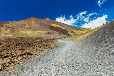 A road between lava hills and fields with lava stone. Mount Etna, Sicily, Italy