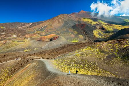 Beautiful valley landscape of The Mount Etna, Sicily, Italy. Colorful lava hills covered with plants and grass. People walking along the road between volcanic rocks and craters