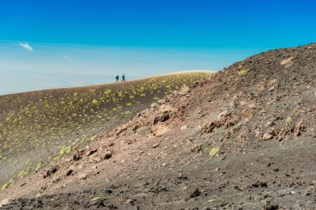 Two tourists do a hiking tour around the edge of a volcanic crater, Mount Etna, Sicily, Italy