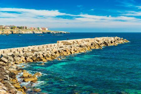 A stone pier in Ortygia, Syracuse, Sicily, Italy. A man walking on a pier towards coastline