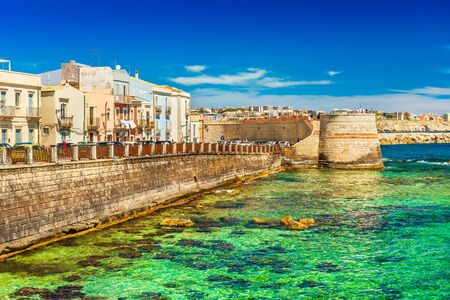 View of an embankment in Ortigia. Picturesque view of the historical part of Syracuse. Beautiful coastline with green-blue, transparent water of The Ionian Sea, Sicily, Italy