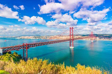 The 25th April Bridge (Ponte 25 de Abril) in Lisbon, Portugal. Picturesque skyline with beautiful sky