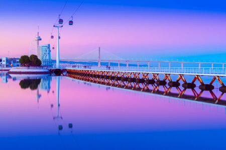 Evening cityscape of Lisbon mirrored in the water, Portugal. View of Park of the Nations (Parque das Nações) at dusk