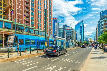 Oslo - June 2019, Norway: A street in the central part of Oslo with modern buildings, tram and taxi car Sajtókép