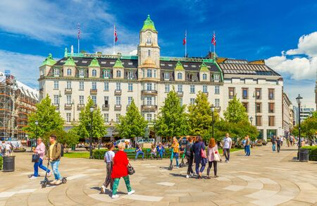 Oslo - June 2019, Norway: View of the Grand Hotel Oslo and people walking around