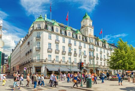 Oslo - June 2019, Norway: View of the Grand Hotel Oslo and people crossing the road near it Sajtókép