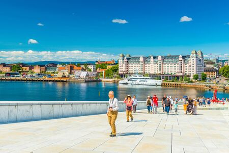 Oslo - June 2019, Norway: Beautiful cityscape of Oslo on a summer day. A group of tourists climbing up to the observation point on top of the Opera House