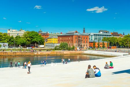 Oslo - June 2019, Norway: View of an embankment in the central part of Oslo. Cityscape with people walking near the Opera House Sajtókép