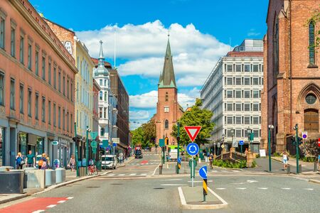 Oslo - June 2019, Norway: View of St. Olavs Cathedral in the center of Oslo. A street with historical architecture and walking people