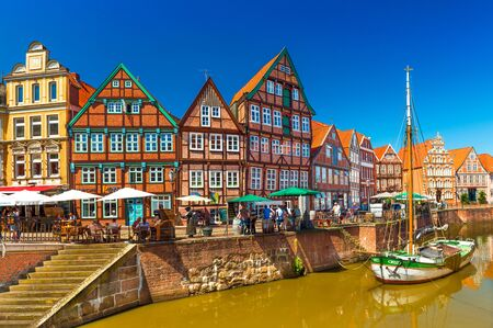 Stade - July 2019, Germany: Cityscape of a small, beautiful German town with the traditional half-timbered architecture and canal with an old wooden sailboat Sajtókép