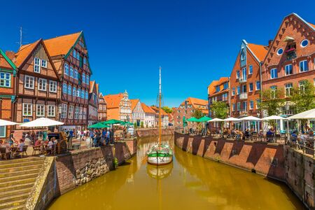 Stade - July 2019, Germany: View of a small German town with traditional architecture, canal with old wooden ship and clear blue sky Sajtókép