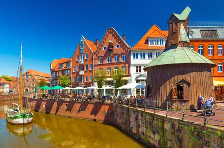 Stade - July 2019, Germany: View of a small German town with the traditional architecture, promenade with walking people and canal with an old wooden ship