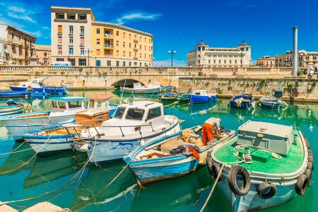 Syracuse - April 2019, Sicily, Italy: Cityscape of Syracuse with colorful boats, bridge and historical buildings with blue sky in the background Sajtókép