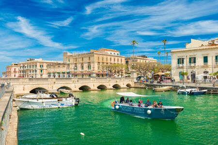 Syracuse - May 2019, Italy: Cityscape of Ortygia with Umbertino Bridge (Ponte Umbertino), old historical buildings and a boat with tourists