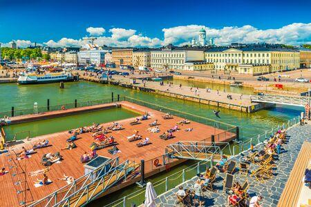 Helsinki - June 2019, Finland: Cityscape of Helsinki harbour with people taking sun bath on a pier
