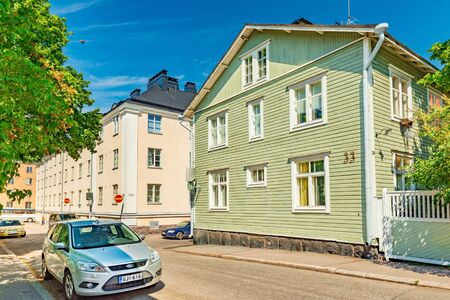 Helsinki - June 2019, Finland: Beautiful street with colorful houses in the traditional architectural style and parked cars Sajtókép