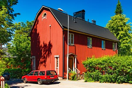 Helsinki - June 2019, Finland: Red wooden residential house on one of the streets in neighbourhood Helsinki. A red car parked near an old house