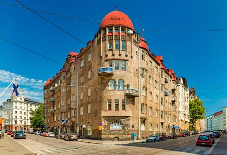 Helsinki - June 2019, Finland: A building in the historical part of Helsinki. View of a street with parked cars and an old building Sajtókép