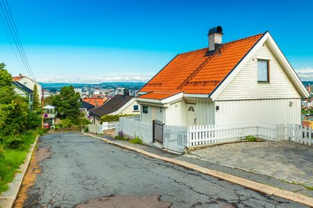 Oslo - June 2019, Norway: View of an empty street on one of the hills around the city. Wooden white house with orange roof Sajtókép