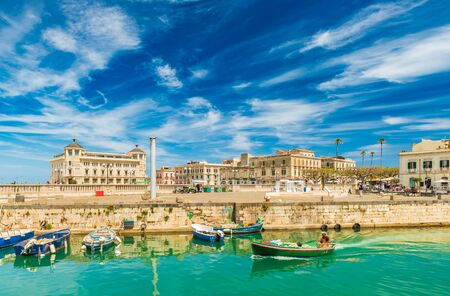 A motorboat sailing along the canal in Ortygia. Cityscape of the famous Sicilian town, Italy Stock fotó