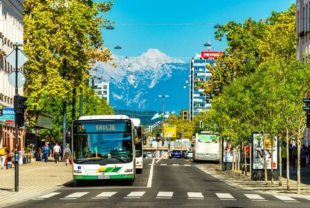 Ljubljana - September 2019, Slovenia: View of a street with public transport, crosswalk, modern architecture and the snowy Alps in the background Sajtókép