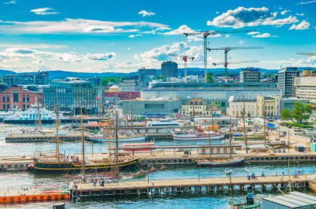 Oslo - June 2019, Norway: Aerial view of the harbor of Oslo with modern and historical ships. Cityscape with modern port, architecture, tower cranes, piers with walking people, hills and the blue sky