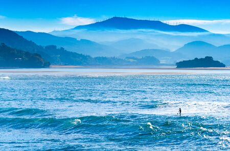 Beautiful landscape with foggy blue hills, ocean, and man on a surfboard