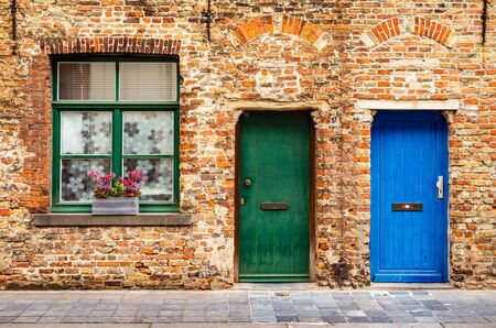 The facade of an old brick house with a window and two wooden doors