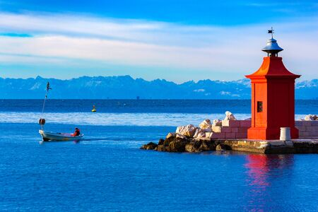 View of the red lighthouse on a pier, a fisherman on a boat and the beautiful mountain range on the horizon, Piran, Slovenia
