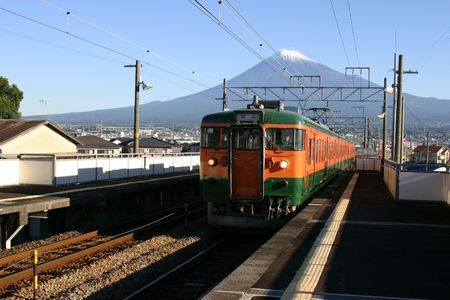 A Japanese local train with Mount Fuji in the background Stock Photo