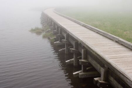 fading: A curved boardwalk on the edge of a lake fading into the mist