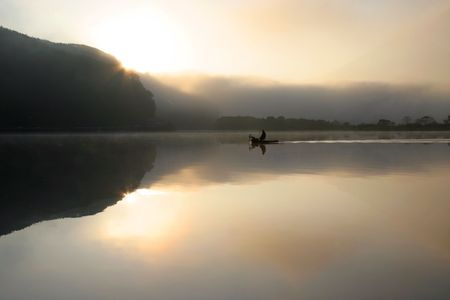 A lone fisherman on a tranquil and misty lake with the sun rising in the background. photo