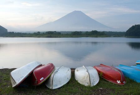 Colorful rowboats on the lakeshore, with Mount Fuji in the background photo