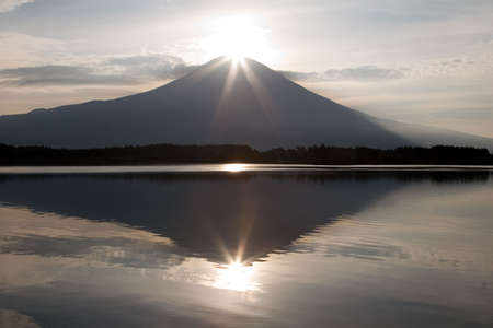 Sunrise over Mount Fuji and its reflection in a nearby lake.