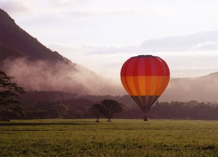 A colorful hot air ballon landing in a misty morning meadow