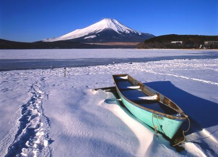 Mount Fuji in Winter with a colorful boat in the foreground.