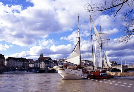 The river Rhine in Basel, Switzerland with a sailboat in the foreground