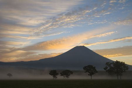 Sunrise with mist and trees over Mount Fuji