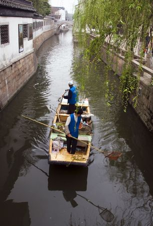 Workers on a canal in Suzhou cleaning the water with nets attached to long bamboo poles. Stock Photo