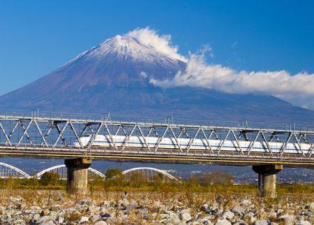 A Japanese bullet train speeding by Mount Fuji