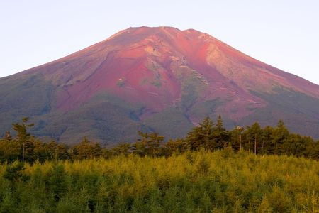 Early morning light on the backside of Mount Fuji shining on wet lava and making the mountain appear red